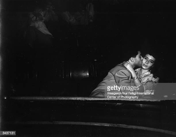 A man kisses his girlfriend at the Palace Theatre while she tries to watch the movie Taken with infrared negative Photo by Weegee/International...