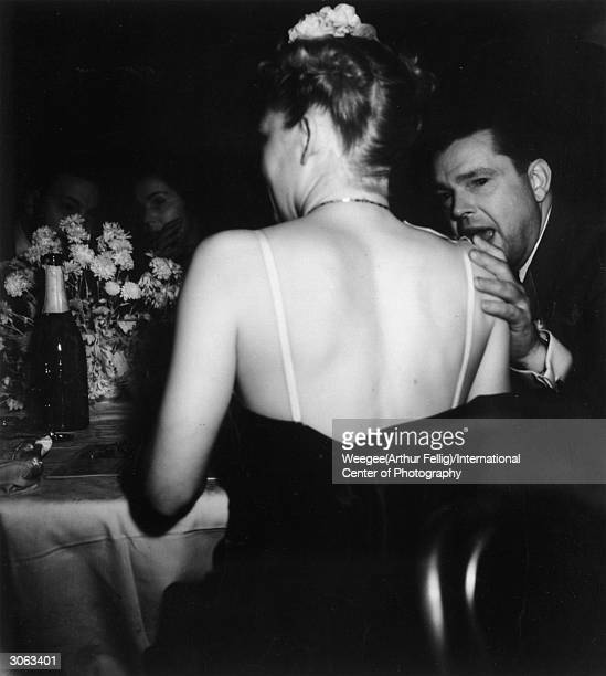 A man places his hand on his ladyfriend's shoulder during an evening at the New York Metropolitan Opera Using infrared negative Photo by...