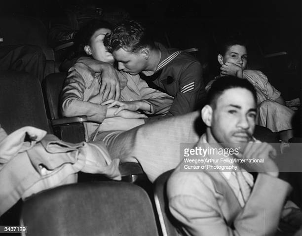 A sailor fondling a girl at the movie theatre Taken with infrared negative Photo by Weegee/International Center of Photography/Getty Images