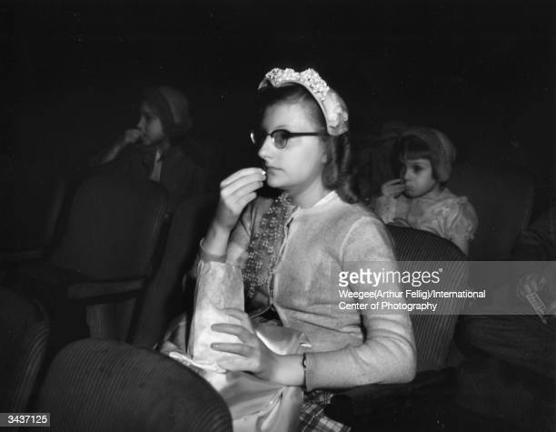 A woman eating popcorn at the movies Taken with infrared negative Photo by Weegee/International Center of Photography/Getty Images