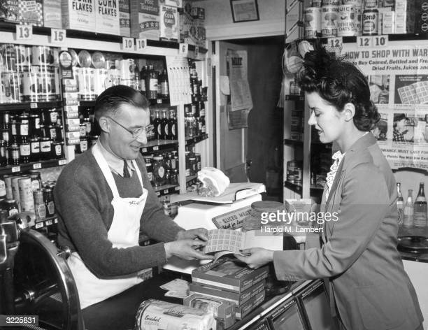 A woman gives war ration tickets to a clerk behind a counter in order to purchase food in a grocery store during World War II Behind the woman a...