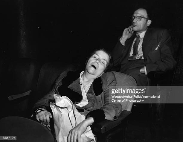 A woman sleeping in her seat at a movie theatre Taken with infrared negative Photo by Weegee/International Center of Photography/Getty Images