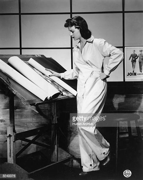 A woman wearing coveralls examines designs on a drafting table World War II