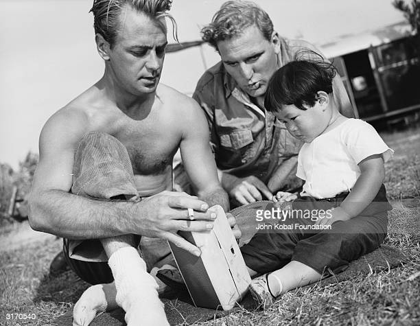 Alan Ladd and William Bendix entertain a small Oriental child during the location filming of 'China' directed by John Farrow