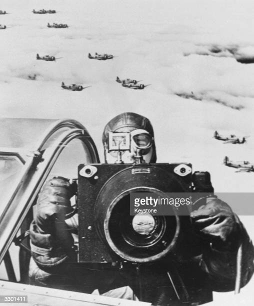 An American Army Air Force photographer in the cockpit of a plane with his camera
