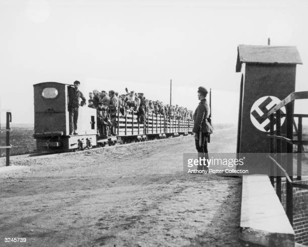 An armed Nazi sentry stands guard as a train full of people enters the gate of a concentration camp during World War II