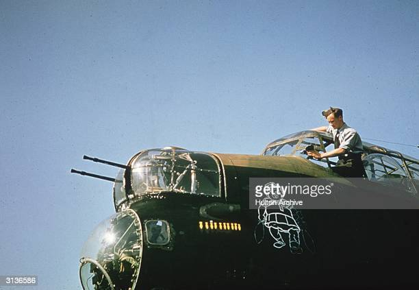 An RAF man cleaning the cockpit windows of a Lancaster bomber