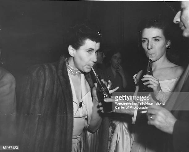 Audience members spend intermission quenching their thirst sipping sodas through a straw during a break at the New York Metropolitan Opera. Using...