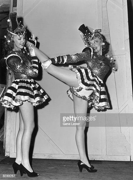 EXCLUSIVE A fulllength image of a showgirl stretching her leg back on another showgirl's shoulder as they warmup backstage for a performance of the...