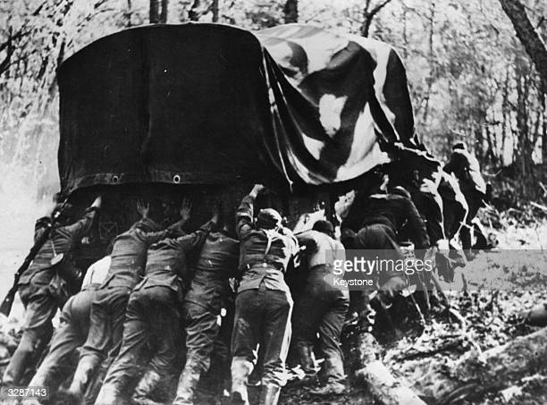 German soldiers pushing a lorry which is stuck in mud in the north west Caucasus