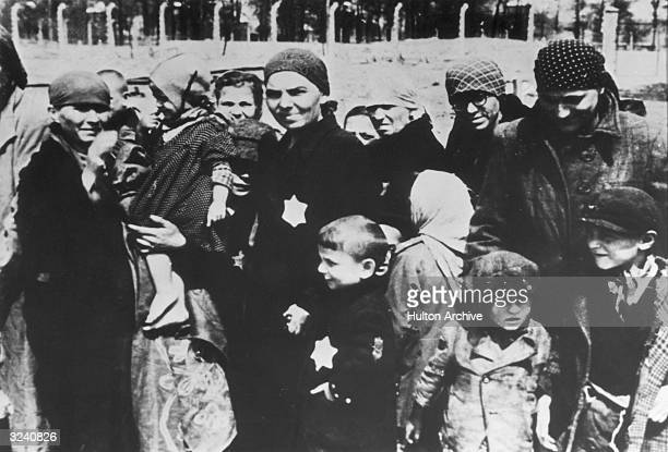 Jewish women and children, some wearing the yellow Star of David patch on their chests, at Auschwitz concentration camp, Poland, undergoing...