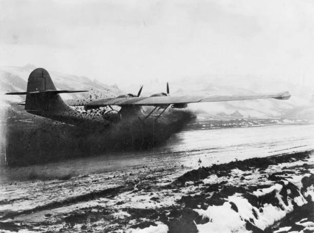 Mud flies as a US Catalina flying boat lands at an...