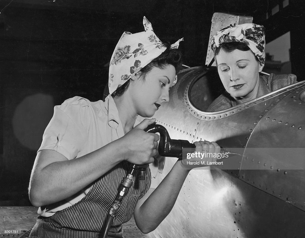 One American female worker drives rivets into an aircraft while another sits in the cockpit on the US home front during World War II. They wear aprons and their hair tucked into scarves. Women who went to work in industries to aid the war effort became known under the moniker 'Rosie the Riveter'.