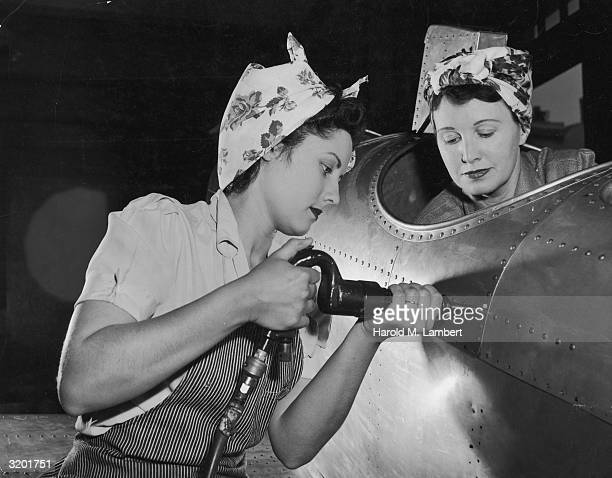 One American female worker drives rivets into an aircraft while another sits in the cockpit on the US home front during World War II They wear aprons...
