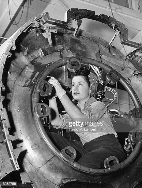 One of the female machinists who are all known as 'Rosie the Riveter' working in a cylinder at an arms manufacturing plant during World War II...