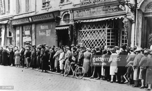 People queuing up hopefully for food in front of a grocery store in a French provincial town during World War II