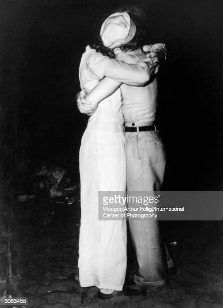 Two lovers caught in a tight embrace on New York's Coney Island beach at nighttime Using infrared negative Photo by Weegee/International Center of...