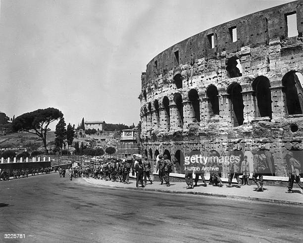 United States troops walk down a curved street past the Coliseum in Rome Italy A Roman gentleman walks in the opposite direction using a cane The...