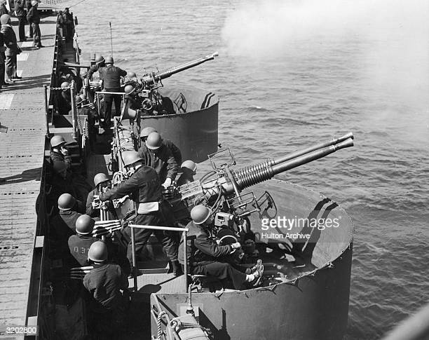 US naval officers load and fire 40MM twin mount antiaircraft guns on the decks of the USS Independence during a naval battle World War II