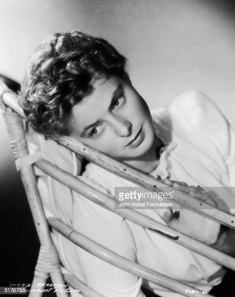 Wearing her hair in a short curly style, film star Ingrid Bergman rests her head against the back of a wicker chair, at the time of her latest film...