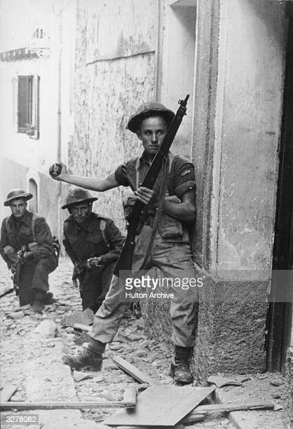 A Canadian soldier preparing to throw a hand grenade into a building whilst comrades shelter behind him