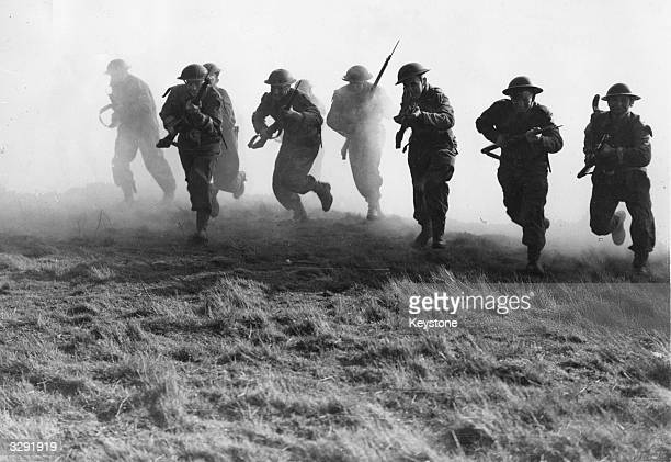Group of Royal Marines shown charging through a smoke screen in a training exercise.