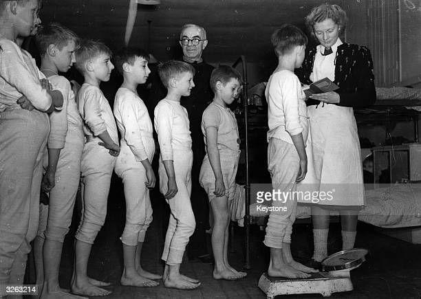 A group of young Dutch boys are weighed at a refugee camp in Sussex