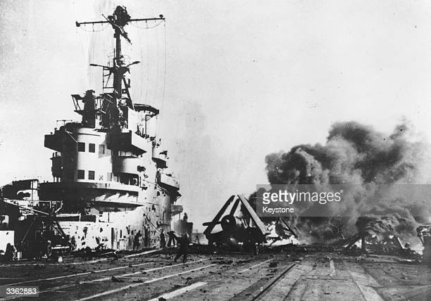 Japanese Kamikaze plane burning on the deck of an allied aircraft carrier.