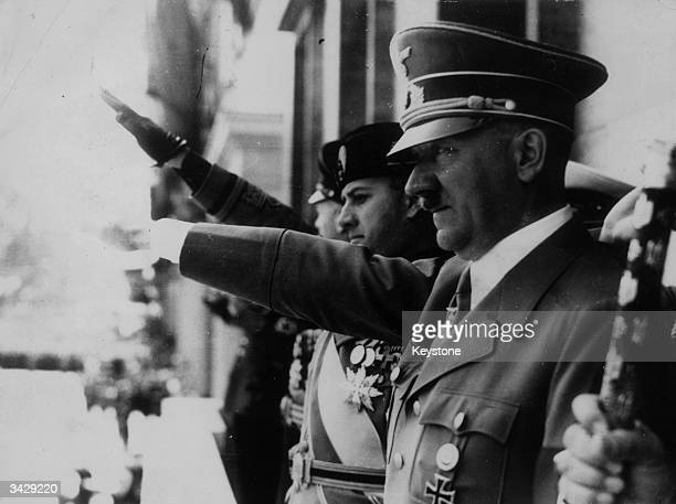 Adolf Hitler gives the fascist salute at a parade during WW II Visible on the balcony with him are Galeazzo Ciano and Italian Benito Mussolini Just...