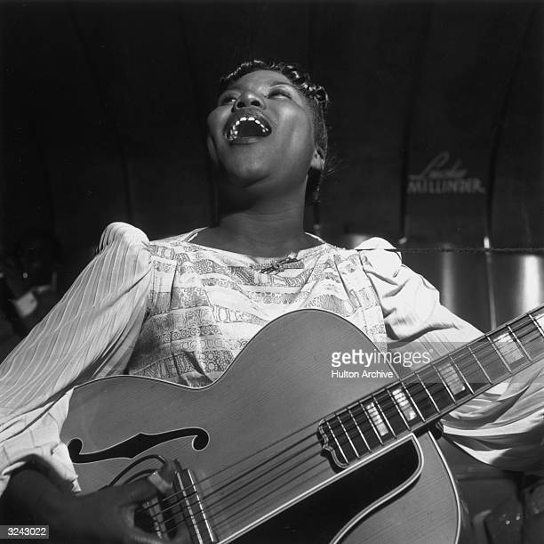 American gospel singer Sister Rosetta Tharpe singing and playing the guitar with the Lucky Millinder Band.