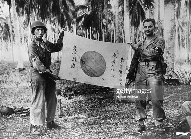 American Marines exhibit a Japanese flag captured on Guadalcanal