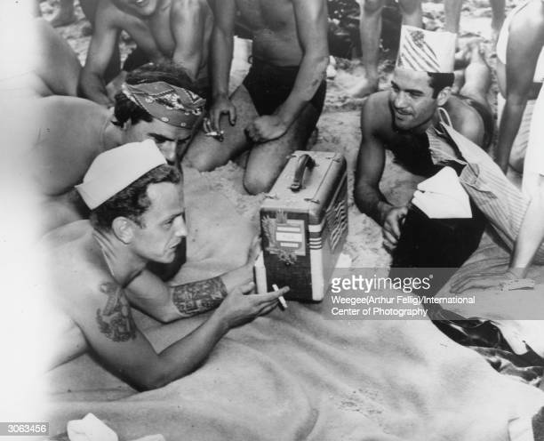 An American sailor listens to the baseball game on the radio whilst subathing on New York's Coney Island beach Photo by Weegee/International Center...