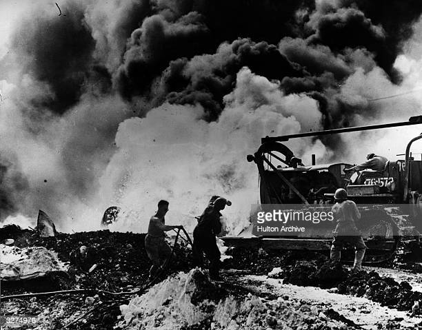 Aviation engineers ram a burning B29 Superfortress with a bulldozer in an attempt to stifle the flames with dirt This follows an attack by the...
