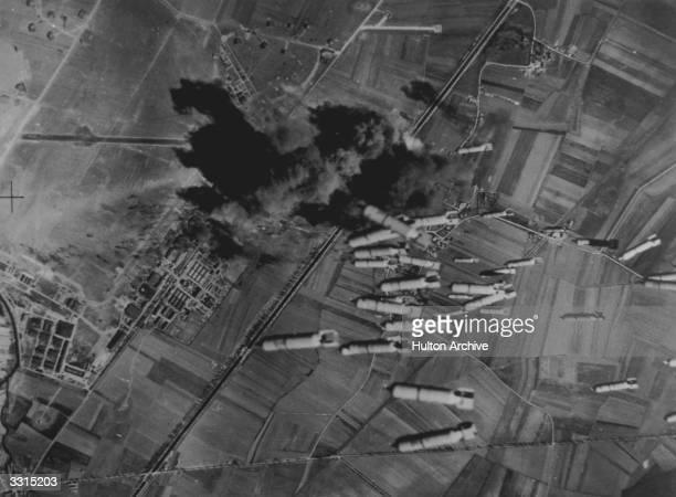 Bombs being dropped on Dijon aerodrome home of the Nazi twin engine fighters by Flying Fortresses of the US Eighth Air Force