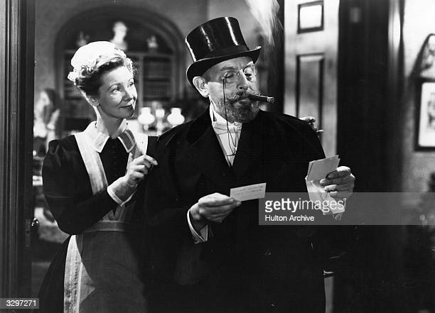 British actor Cedric Hardwicke reads his visiting cards whilst a maid helps him with his cape in a scene from 'The Lodger' in which the lodger is...