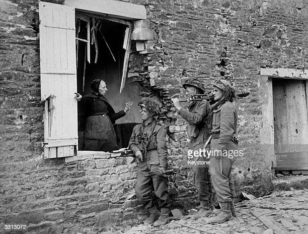 British troops talk to an old lady in a devastated Dutch village