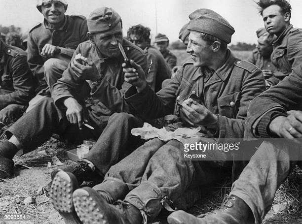 Captured German soldiers on a beach in France eating rations provided by the US Army while awaiting shipment to an internment camp in England.