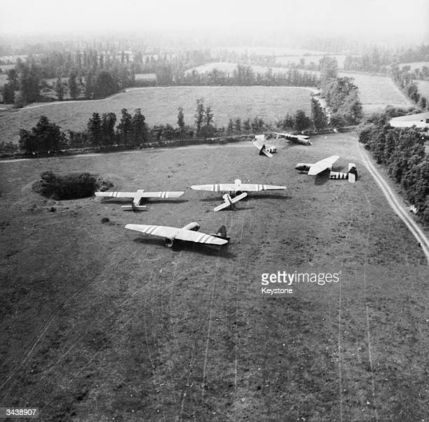 Four British Army Airspeed Horsa gliders with their tails detached for unloading and a Waco Hadrian glider all safely landed in a field Gliders were...
