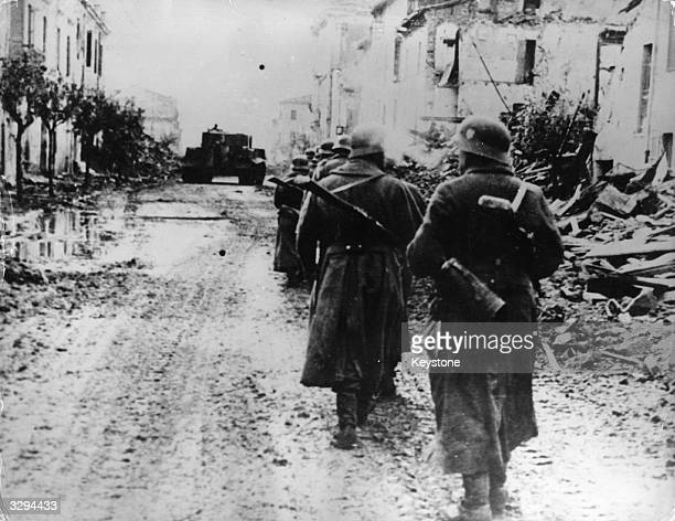German 14th Army troops moving cautiously through an Italian village