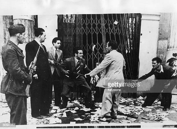 Italian anti-Fascists point their guns at a suspected pro-Fascist. He has been pulled from a shop that the anti-Fascists have just bombed.