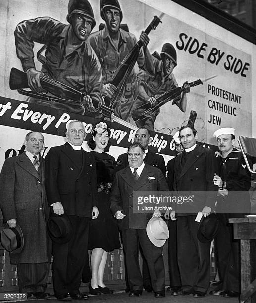 NYC mayor Fiorello La Guardia poses with religious leaders in front of a World War II religious unity poster in Times Square New York City LR Rabbi...