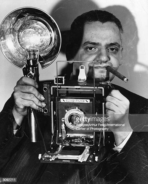 Polish-born American photographer Arthur Fellig with his Speed Graphic camera. He was known by the police as 'Weegee' for his ouija-like prescience...