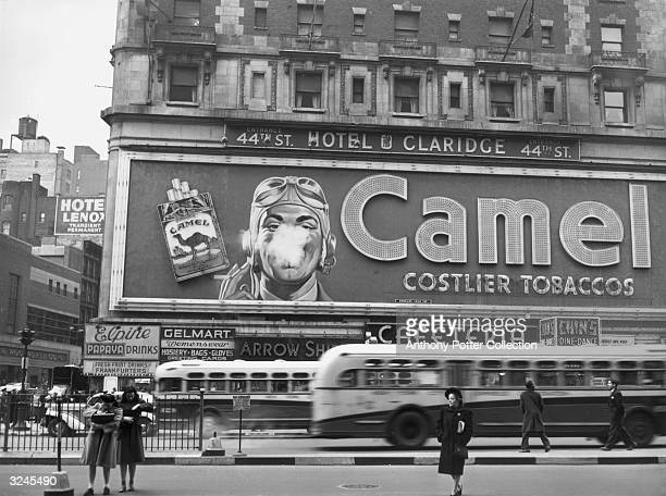 Street scene showing a Camel cigarette billboard with a pilot's face smoking on the exterior of the Claridge Hotel in Times Square, New York City.