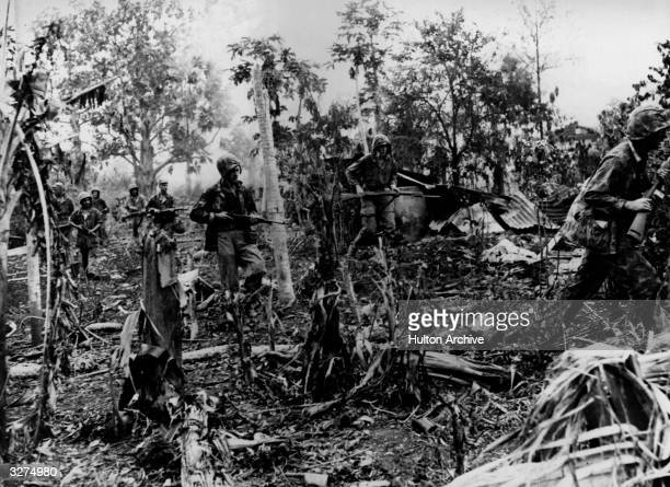 Marines sweep through the jungles of Saipan on the lookout for Japanese snipers.