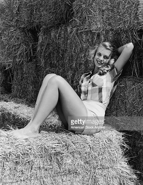 A barefoot blonde woman wearing shorts and plaid shirt poses on a haystack
