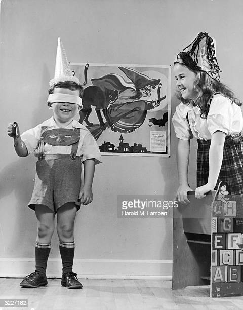 A blindfolded boy wearing a party hat playing pin the tail on a witch poster as a smiling girl looks on