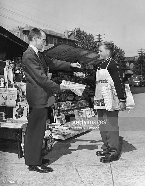 A businessman smiles as he drops some change into a boy's hand to purchase a newspaper in front of a news stand The boy wears a Newsweek apron