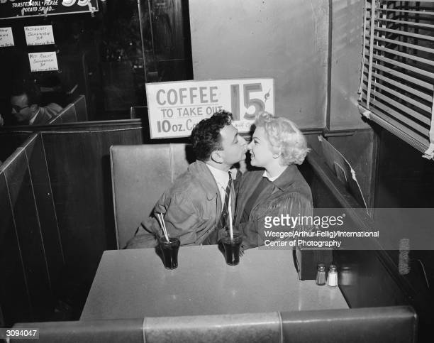 A couple in a cafe booth are about to kiss Photo by Weegee/International Center of Photography/Getty Images