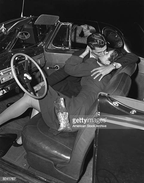 A couple kissing in the front seat of a convertible car at a drivein movie theater 1940s The man in the next car ignores the couple resting his elbow...