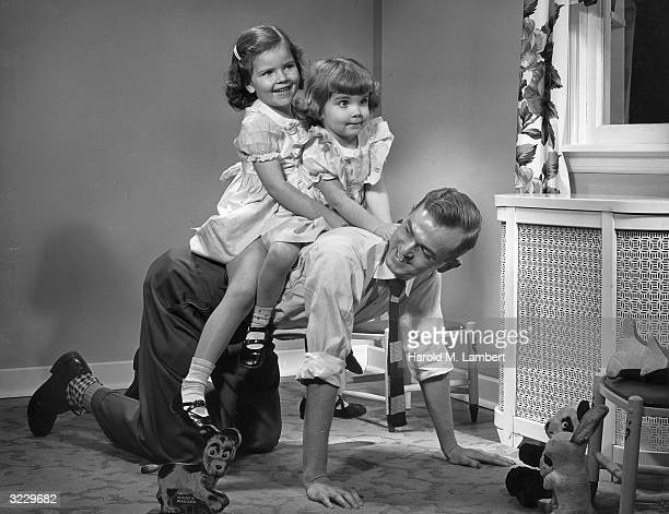 A father crawls on his hands and knees on his living room floor giving his two young daughters a horseback ride 1940s Stuffed animals are strewn on...